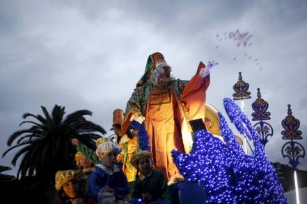 An actor dressed as Melchior, one of the Three Wise Men, throws sweets during the traditional Epiphany parade in Malaga, southern Spain, January 5, 2016. Children in Spain traditionally receive their Christmas presents delivered by the Three Wise Men on the morning of January 6, during the Christian holiday of the Epiphany. REUTERS/Jon Nazca